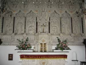 Reredos – A decorative screen or facing on the wall at the back of an altar.